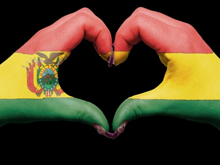 Gesture made by bolivia flag colored hands showing symbol of heart and love photo