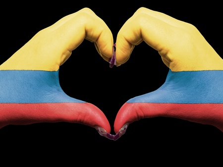 Gesture made by colombia flag colored hands showing symbol of heart and love photo