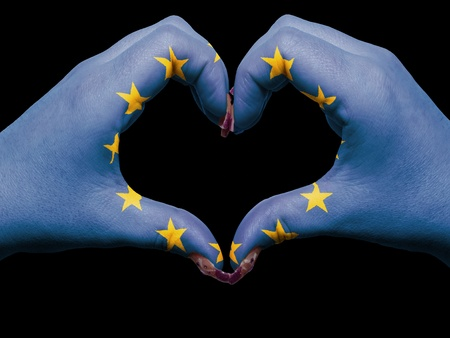 Gesture made by europe flag colored hands showing symbol of heart and love photo
