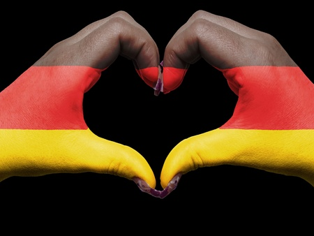 Gesture made by germany flag colored hands showing symbol of heart and love photo