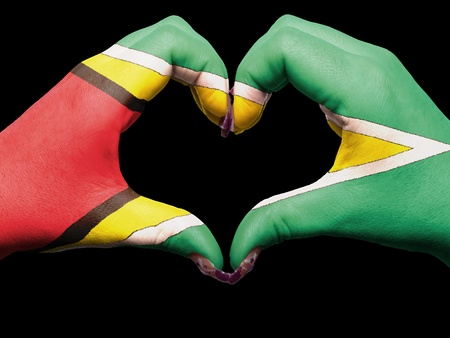 Gesture made by guyana flag colored hands showing symbol of heart and love