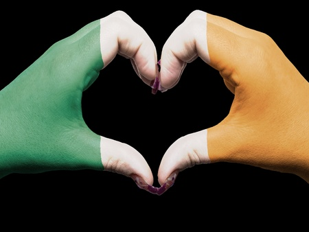 Gesture made by ireland flag colored hands showing symbol of heart and love photo