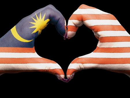 Tourist made gesture  by malaysia flag colored hands showing symbol of heart and love photo