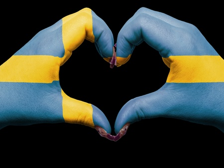 Gesture made by sweden flag colored hands showing symbol of heart and love photo