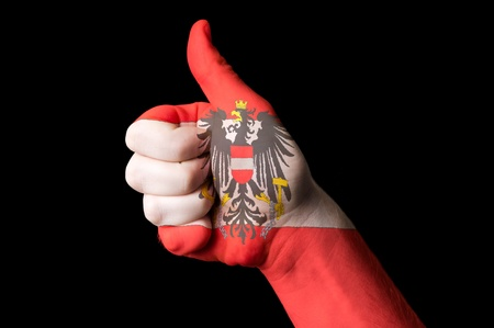 Hand with thumb up gesture colored in austria national flag  photo
