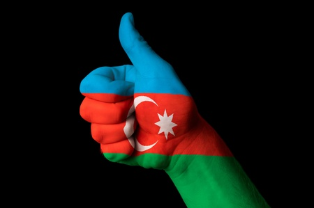 Hand with thumb up gesture in colored azerbaijan national flag photo
