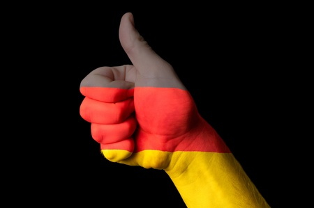 Hand with thumb up gesture colored in germany national flag  photo