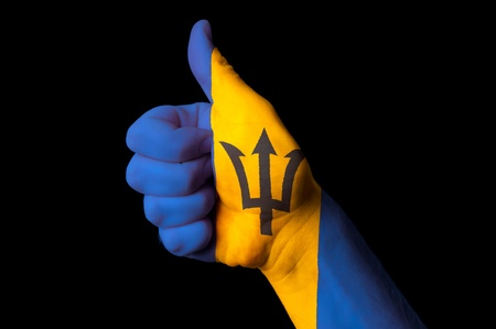 barbadian: Hand with thumb up gesture in colored barbados national flag as symbol of excellence, achievement, good, - for tourism and touristic advertising, positive political, cultural, social management of country Stock Photo