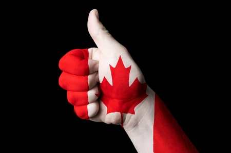 canadian flag: Hand with thumb up gesture in colored canada national flag as symbol of excellence, achievement, good, - for tourism and touristic advertising, positive political, cultural, social management of country Stock Photo
