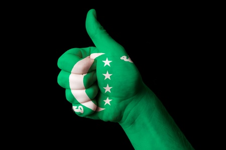 comoros: Hand with thumb up gesture in colored comoros national flag as symbol of excellence, achievement, good, - for tourism and touristic advertising, positive political, cultural, social management of country