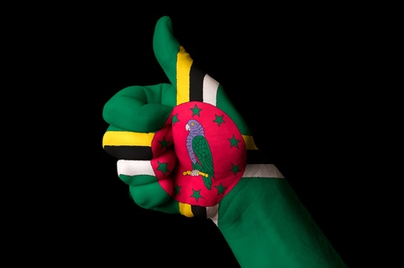 Hand with thumb up gesture in colored dominican national flag as symbol of excellence, achievement, good, - for tourism and touristic advertising, positive political, cultural, social management of country photo