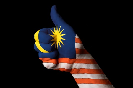 touristic: Hand with thumb up gesture in colored malaysia national flag as symbol of excellence, achievement, good, - for tourism and touristic advertising, positive political, cultural, social management of country