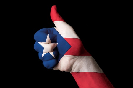 Hand with thumb up gesture in colored puertorico national flag as symbol of excellence, achievement, good, - for tourism and touristic advertising, positive political, cultural, social management of country