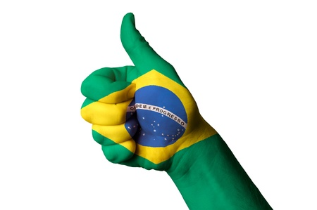 Hand with thumb up gesture in colored brazil national flag as symbol of excellence, achievement, good, - for tourism and touristic advertising, positive political, cultural, social management of country Stock Photo