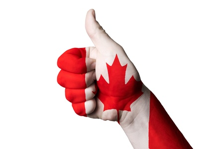 winning flag: Hand with thumb up gesture in colored canada national flag as symbol of excellence, achievement, good, - for tourism and touristic advertising, positive political, cultural, social management of country Stock Photo