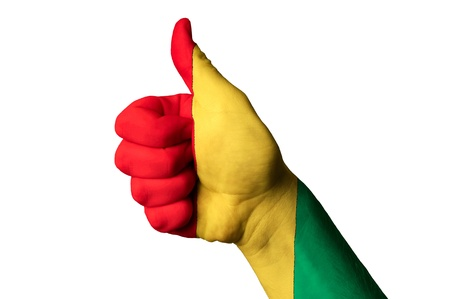 Hand with thumb up gesture in colored guinea national flag as symbol of excellence, achievement, good, - for tourism and touristic advertising, positive political, cultural, social management of country Stock Photo - 13208071