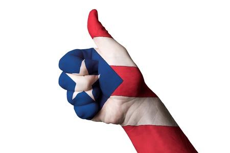 bandera de puerto rico: Mano con el pulgar arriba gesto en color puertorico bandera nacional como s�mbolo de excelencia, logro, bueno, - para el turismo y la publicidad tur�stica, la gesti�n positiva pol�tico, cultural, social del pa�s