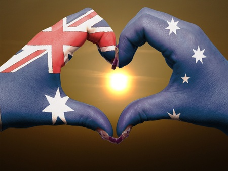 Tourist made gesture  by australia flag colored hands showing symbol of heart and love during sunrise photo