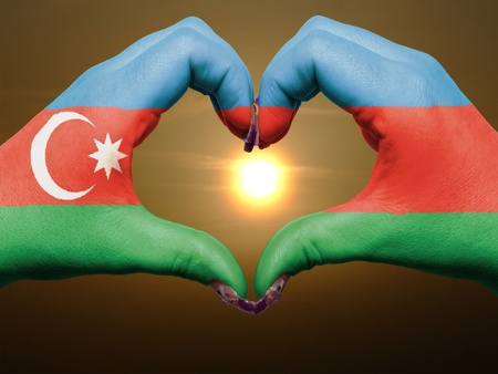 azerbaijani: Tourist made gesture  by azerbaijan flag colored hands showing symbol of heart and love during sunrise