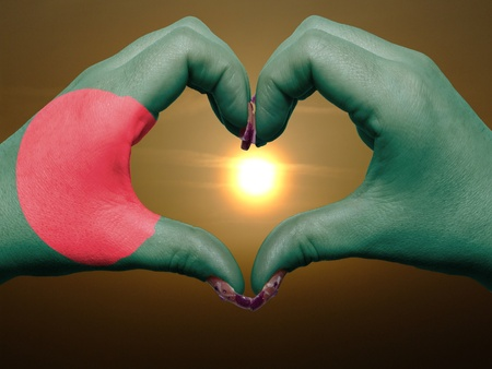 Tourist made gesture  by bangladesh flag colored hands showing symbol of heart and love during sunrise