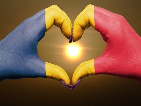 Tourist made gesture  by chad flag colored hands showing symbol of heart and love during sunrise Stock Photo - 13564025