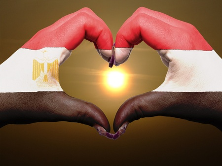 Tourist made gesture  by egypt flag colored hands showing symbol of heart and love during sunrise photo