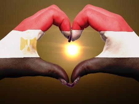 flag of egypt: Turismo hizo un gesto con las manos la bandera de colores que muestran egipto s�mbolo del coraz�n y el amor durante el amanecer