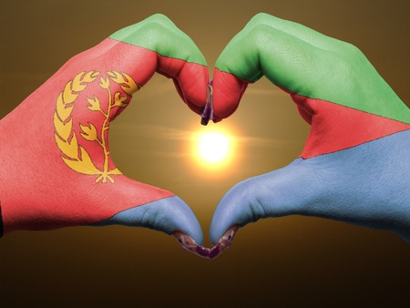 eritrea: Tourist made gesture  by eritrea flag colored hands showing symbol of heart and love during sunrise