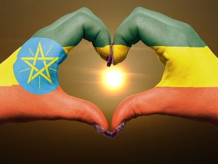 Tourist made gesture  by ethiopia flag colored hands showing symbol of heart and love during sunrise photo