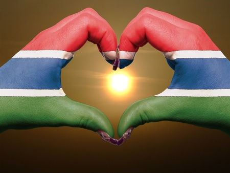 Tourist made gesture  by gambia flag colored hands showing symbol of heart and love during sunrise photo