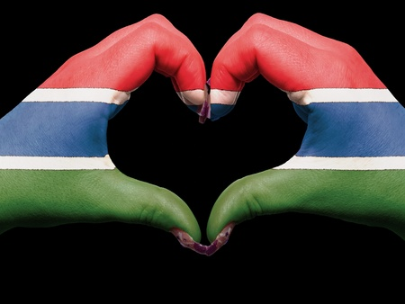Tourist made gesture  by gambia flag colored hands showing symbol of heart and love photo