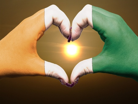 Tourist made gesture  by cote d'ivore flag colored hands showing symbol of heart and love during sunrise Stock Photo - 13564015
