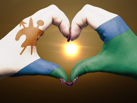 Tourist made gesture  by lesotho flag colored hands showing symbol of heart and love during sunrise photo