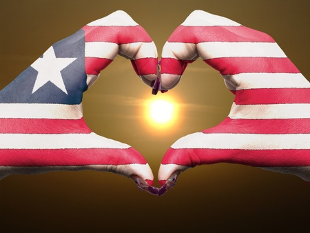 Tourist made gesture  by liberia flag colored hands showing symbol of heart and love during sunrise photo