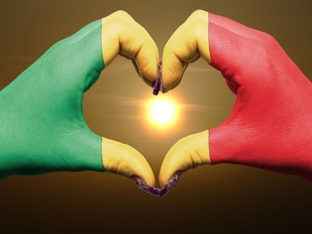 Tourist made gesture  by mali flag colored hands showing symbol of heart and love during sunrise photo