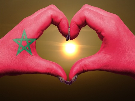 made in morocco: Tourist made gesture  by morocco flag colored hands showing symbol of heart and love during sunrise