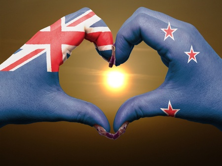 new zealand flag: Tourist made gesture  by new zealand flag colored hands showing symbol of heart and love during sunrise