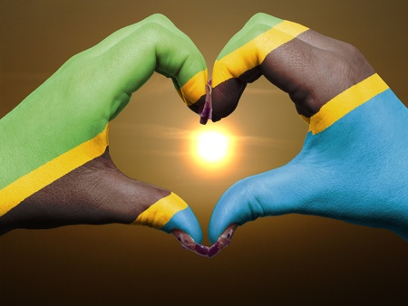 Tourist made gesture  by tanzania flag colored hands showing symbol of heart and love during sunrise photo
