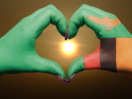 zambia flag: Tourist made gesture  by zambia flag colored hands showing symbol of heart and love during sunrise Stock Photo