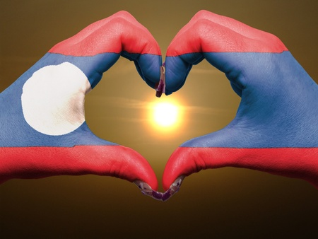 lao: Tourist made gesture  by laos flag colored hands showing symbol of heart and love during sunrise