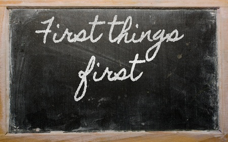 handwriting blackboard writings - First things first Stock Photo - 13564075