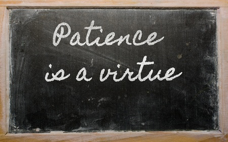 patience: handwriting blackboard writings - Patience is a virtue Stock Photo