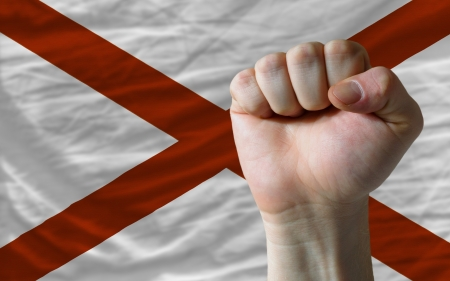 determinism: complete american state of alabama flag covers whole frame, waved, crunched and very natural looking. In front plan is clenched fist symbolizing determination