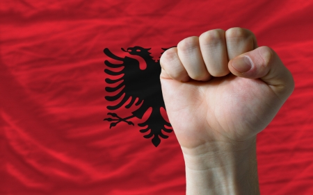 complete national flag of albania covers whole frame, waved, crunched and very natural looking. In front plan is clenched fist symbolizing determination photo