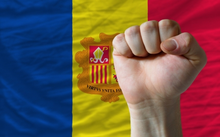 complete national flag of andorra covers whole frame, waved, crunched and very natural looking. In front plan is clenched fist symbolizing determination Stock Photo - 13953394