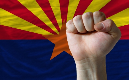 determinism: complete american state of arizona flag covers whole frame, waved, crunched and very natural looking. In front plan is clenched fist symbolizing determination