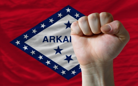 determinism: complete american state of arkansas flag covers whole frame, waved, crunched and very natural looking. In front plan is clenched fist symbolizing determination Stock Photo