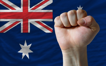 complete national flag of australia covers whole frame, waved, crunched and very natural looking. In front plan is clenched fist symbolizing determination photo