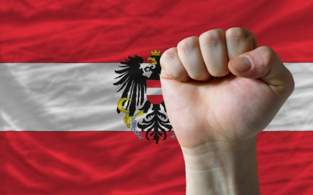 determinism: complete national flag of austria covers whole frame, waved, crunched and very natural looking. In front plan is clenched fist symbolizing determination Stock Photo