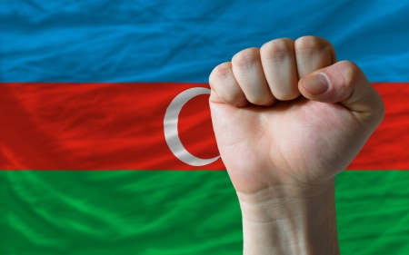 determinism: complete national flag of azerbaijan covers whole frame, waved, crunched and very natural looking. In front plan is clenched fist symbolizing determination